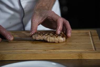 Carve the veal entrecote into slices.